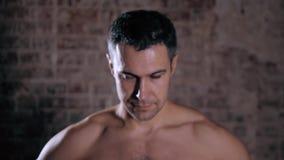 Modelo masculino maduro hermoso que coloca cierre con las tetas al aire encima del retrato en el fondo del ladrillo, hombre serio almacen de video