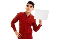 Modelo masculino moreno atractivo de Youn en la camisa roja que presenta con el cartel vacío en sus manos y que mira la cámara Imágenes de archivo libres de regalías
