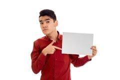 Modelo masculino moreno divertido de Youn en la camisa roja que presenta con el cartel vacío en sus manos y que mira la cámara ai Imagen de archivo
