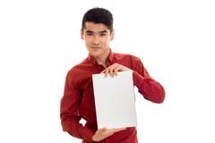 Modelo masculino moreno elegante de Youn en la camisa roja que presenta con el cartel vacío en sus manos y que mira la cámara ais Foto de archivo libre de regalías