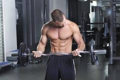 Modelo masculino muscular hermoso en una posición derecha que hace el bíceps imagenes de archivo