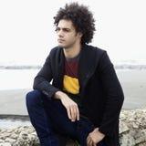 Modelo masculino pensativo que se sienta en rocas delante del océano foto de archivo libre de regalías