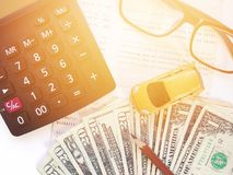 Modelo miniatura del coche, lápiz, dinero, calculadora, lentes y libreta de banco del cuenta de ahorros o estado financiero sobre Fotos de archivo libres de regalías