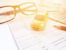Modelo miniatura del coche, lápiz, lentes, libreta de banco del dinero y de ahorros del cuenta o estado financiero sobre el fondo Imagen de archivo libre de regalías