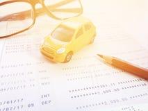 Modelo miniatura del coche, lápiz, lentes y libreta de banco del cuenta de ahorros o estado financiero sobre el fondo blanco Imágenes de archivo libres de regalías