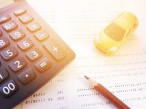 Modelo miniatura del coche, libreta de banco del lápiz, de la calculadora y del cuenta de ahorros o estado financiero sobre el fo Fotos de archivo libres de regalías