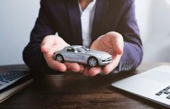 Modelo miniatura del coche a mano, representación auto y concepto del alquiler imagen de archivo