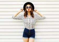 Modelo ? moda da jovem mulher no chap?u redondo preto, short, camisa listrada branca que levanta na parede branca fotos de stock