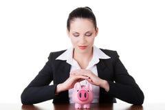Modelo moderno del banco. Mujer de negocios que se sienta con la hucha. Fotos de archivo libres de regalías
