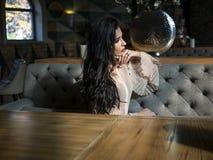 Modelo moreno bonito que senta-se em uma tabela em um restaurante e em um levantamento modelo da foto na sess?o de foto foto de stock