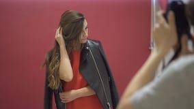 Modelo moreno bonito que veste um casaco de cabedal que está sendo fotografado filme