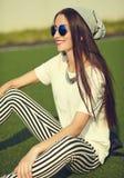 Modelo moreno de la mujer en la ropa casual del inconformista del verano que presenta en fondo de la calle en el parque Fotos de archivo libres de regalías