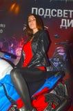Modelo moreno de olhos castanhos do parque 2015 de Moto em uma motocicleta Imagem de Stock Royalty Free