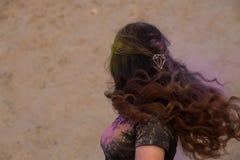 Modelo moreno maravilhoso com o cabelo de vibração longo que veste a camisa preta de t coberta com a pintura seca colorida Holi n imagens de stock
