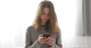 Modelo moreno novo na mensagem de datilografia da camiseta cinzenta no telefone celular que está perto da janela filme