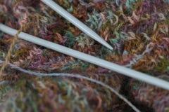 Modelo multicolor hecho punto de las lanas del hilado con las agujas que hacen punto Foto de archivo libre de regalías