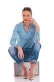 Modelo na pose da sarja de Nimes assentado no fundo do estúdio com mão no kne imagem de stock royalty free
