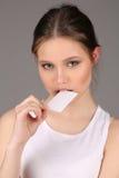 Modelo no cartão bitting da camiseta interioa branca Fim acima Fundo cinzento Imagens de Stock Royalty Free