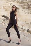 Modelo no catsuit preto e nos saltos cravados Fotografia de Stock Royalty Free