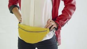 Modelo no revestimento vermelho e poses pretas da calças com bloco de nádegas amarelo nos quadris durante a sessão fotográfica Te filme