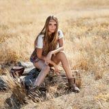 Modelo novo bonito que senta-se em um coto em um campo no nascer do sol - disparou fora Imagem de Stock