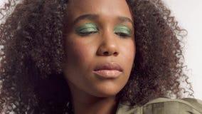 Modelo novo da raça misturada no estúdio no branco com cabelo encaracolado, composição verde-clara do olho filme
