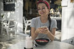 Modelo novo de encantamento com sorriso bonito usando o telefone moderno, lendo a boa notícia imagem de stock