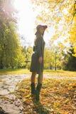 Modelo novo glorioso no vestido cinzento da malha e no chapéu vermelho que levantam no th Foto de Stock Royalty Free
