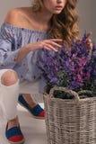 Modelo novo na blusa e nas calças de brim que levantam ao lado da cesta das flores fotografia de stock royalty free