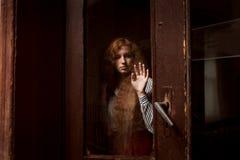 Modelo pelirrojo hermoso que se coloca detrás de una puerta de cristal cerrada Foto de archivo libre de regalías