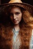 Modelo pelirrojo joven atractivo con el pelo rizado en el sombrero de paja p Fotos de archivo libres de regalías