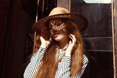 Modelo pelirrojo joven atractivo en sombrero de paja con la sombra encendido él Imagen de archivo
