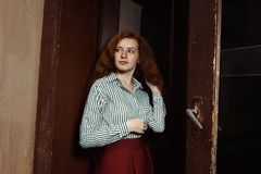 Modelo pelirrojo joven glorioso en camisa stripred y falda roja Fotografía de archivo