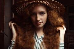 Modelo pelirrojo joven hermoso con el pelo rizado en el sombrero de paja po Imagenes de archivo