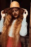 Modelo pelirrojo joven hermoso con el pelo rizado largo en la paja h Imagen de archivo