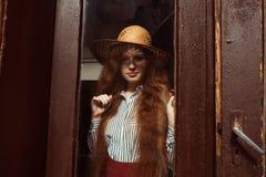 Modelo pelirrojo joven hermoso en sombrero de paja con la sombra en ella Fotografía de archivo