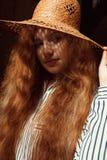 Modelo pelirrojo joven precioso con el pelo ondulado largo en sombrero de paja Fotos de archivo