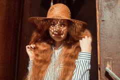 Modelo pelirrojo joven sonriente en sombrero de paja con la sombra en su f Fotografía de archivo