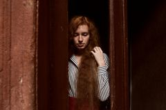 Modelo pelirrojo triste que se coloca detrás de una puerta de cristal cerrada Raindr Imagenes de archivo