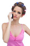 Modelo pensativo en rodillos del pelo en el teléfono Foto de archivo libre de regalías