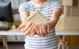 Modelo pequeno da casa na mão da mulher Escritório domiciliário, conceito dos bens imobiliários do negócio foto de stock royalty free