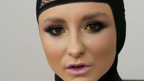 Modelo profissional novo da menina com composição bonita e os olhos marrons que levantam em um tampão preto em sua cabeça na fren video estoque