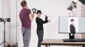 Modelo profissional que veste um chapéu e um fotógrafo que tomam imagens dela vídeos de arquivo