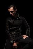 Modelo punk no levantamento do casaco de cabedal assentado no estúdio escuro imagem de stock royalty free