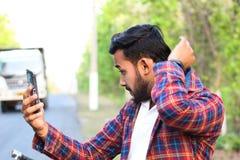 Modelo que mira su móvil y que pone en cortocircuito su camisa foto de archivo libre de regalías