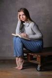 Modelo que se sienta con el libro que toca su cabeza Fondo gris Imagen de archivo libre de regalías