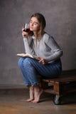Modelo que se sienta con el libro y el vidrio de vino Fondo gris Fotos de archivo libres de regalías