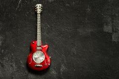 Modelo rojo de la guitarra del juguete con la cara de reloj Fotos de archivo