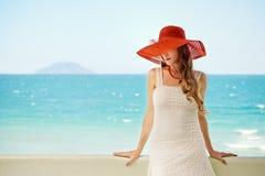 Modelo romântico bonito no chapéu vermelho com os bordos vermelhos que olham a came Imagem de Stock Royalty Free