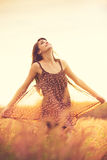 Modelo romântico no vestido de Sun no campo dourado no por do sol Imagem de Stock